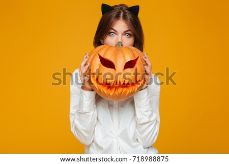Photo of shocked young woman dressed in crazy cat halloween costume over yellow background with pumpkin.