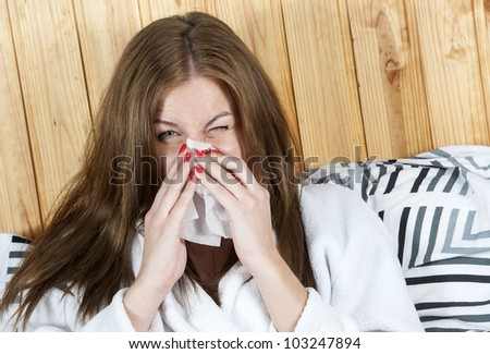 Photo of sick woman sitting in bed with tissue and blowing her nose into it
