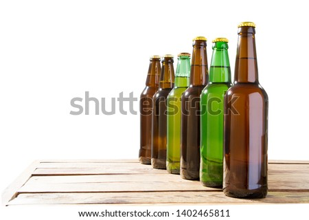 Photo of six different full beer bottles with no labels. Separate clipping path for each bottle included. six 6 separate photos merged together. Beer bottles on table isolated copy space