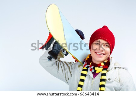 Photo of skillful teenager with snowboard on his shoulder over blue background