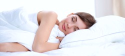 Photo of sleeping young woman lying in bed with eyes closed. Attractive beautiful bedroom bedtime caucasian closed comfort comfortable morning pajamas pillow relax rest sleep wellness white young