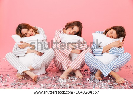 Photo of sleepy women 20s wearing leisure clothings holding pillows and taking pleasure during slumber party isolated over pink background Stock photo ©