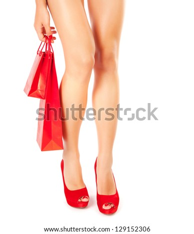 Photo of slim female legs wearing red stylish shoes on high heels isolated on white background, holding in hand paper bag with gift, luxury lifestyle, hot woman, fashionable footwear, shopping concept
