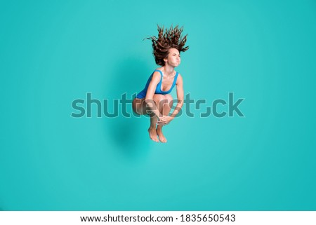 Photo of slim thin slender girl rest relax resort jump springboard dive water pool hold breath, hands legs wear blue bodysuit isolated over turquoise color background