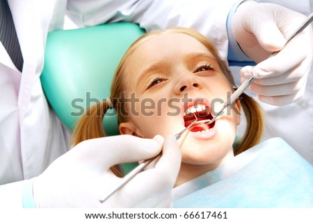 Photo of small girl with open mouth while it being examined by dentist