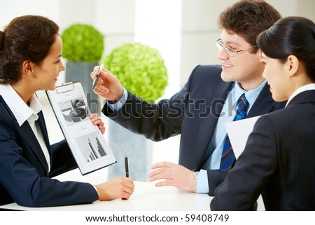 Photo of smart business team discussing documents in the office