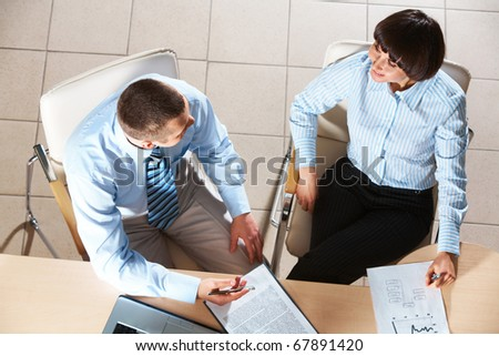 Photo of smart businessman and employee interacting in office