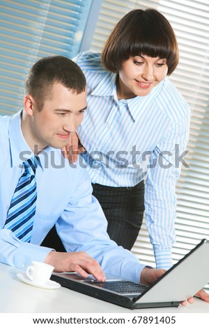 Photo of smart businessman and secretary looking at laptop screen at meeting