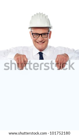 Photo of smart senior architect in helmet holding blank placard over white background