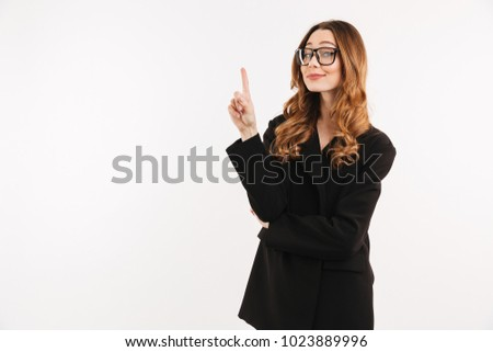 Photo of smart sexual woman in black jacket and eyeglasses smiling and pointing index finger up on copyspace isolated over white background