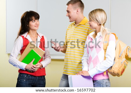 Photo of smart teenager standing and explaining something to serious girl in college