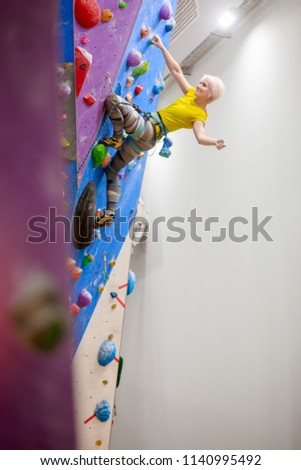 Stock Photo Photo of smiling girl with bag for talc climbing on wall in gym