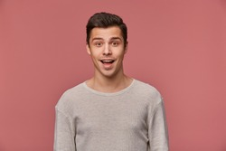 Photo of smiling handsome young guy wears in blank long sleeve, looks at the camera with happy expression, stands over pink background.