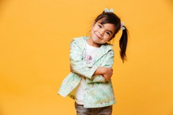 Photo of smiling little girl child standing isolated over yellow background. Looking camera.