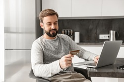 Photo of smiling man 30s in casual wear sitting alone in apartment and using laptop with credit card for shopping online