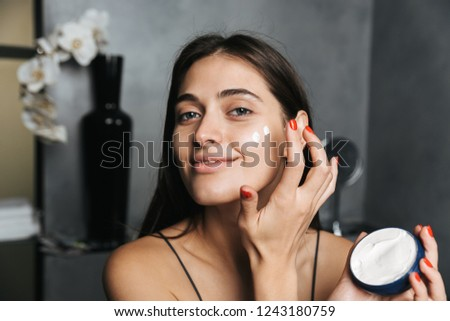 Photo of smiling woman with long dark hair standing in bathroom and applying moisturizing cream on face