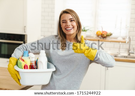 Photo of smiling young woman housewife in gloves holding cleanser bottles and showing thumb up at modern kitchen