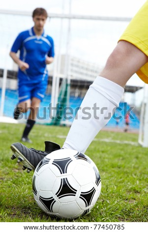 Photo of soccer ball being kicked by footballer during game