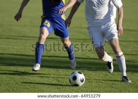 Photo of soccer players with ball in action