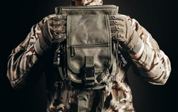 Photo of soldier in camouflaged uniform and tactical gloves holding leg bag on black background close-up view.