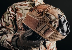 Photo of soldier in camouflaged uniform and tactical gloves holding military helmet with cover on black background.