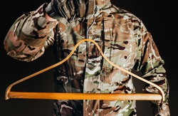 Photo of soldier in camouflaged uniform and tactical gloves holding wooden shirt hanger on black background.