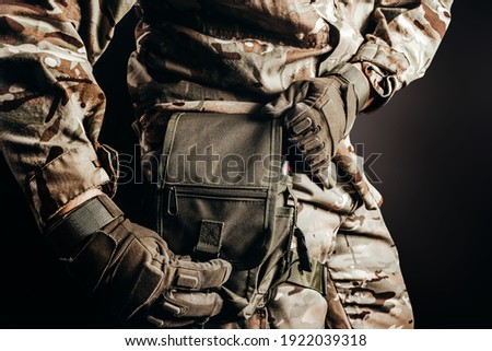 Photo of soldier in camouflaged uniform and tactical gloves using leg bag on black background. Foto stock ©
