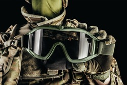 Photo of soldier in level 3 armored vest ammunition, tactical gloves holding tactical goggles on black background.