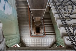 Photo of spiral staircase in residential house. Typical building in historical center in Saint Petersburg, Russia. Steps with forged fence. Diamond shaped tile on the floor. Apartment house. Dom Baka.
