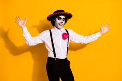 Photo of spooky funky guy crazy attempt jump scare appear from nowhere surprise everyone carnival wear white shirt rose death costume sombrero suspenders isolated yellow color background