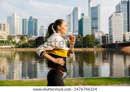 Photo of sporty slim woman wearing sportswear running while working out near city riverfront