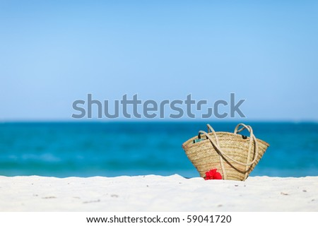 Photo of straw beach bag and red hibiscus flowers on exotic white sand beach with room for text and copyspace
