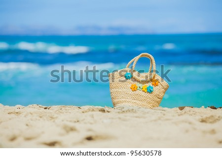 Photo of straw beach bag with flowers on exotic white sand beach