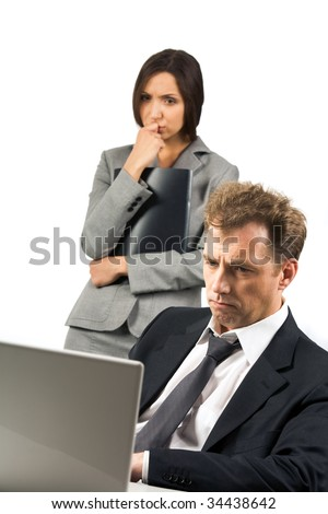 Photo of stressed businessman looking at laptop screen with scared woman at background