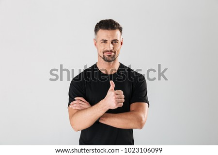 Photo of strong sportsman standing isolated over grey wall background. Looking camera showing thumbs up.