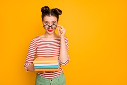 Photo of student nerd lady hold many books look tricky taking off funny freak glasses wear striped red white shirt green pants isolated bright yellow color background