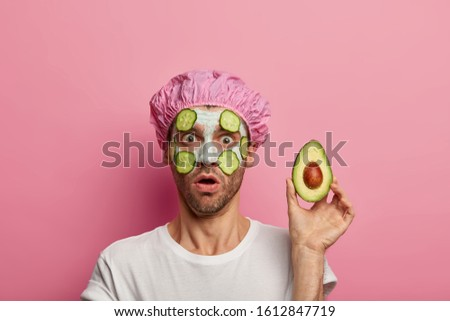Photo of stunned man gasps from wonder, holds avocado near face, surprised by effect of clay mask, wears bath cap, has bristle, isolated over pink studio wall. Beauty, wellness, skin care, cosmetology