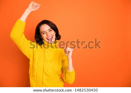 Photo of stunned shocked surprised with victory girlfriend rejoicing her having won something creating copyspace while isolated with orange background