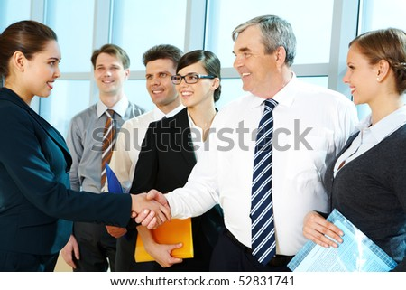 Photo of successful associates handshaking after striking deal with partners near by