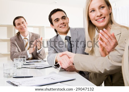 Photo of successful business partners handshaking after striking deal while their colleagues applauding