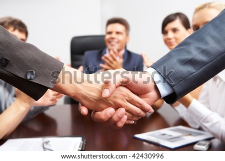 Photo of successful business partners handshaking after striking great deal with applauding people at background