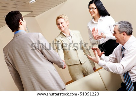 Photo of successful business partners handshaking after striking great deal with applauding people near by