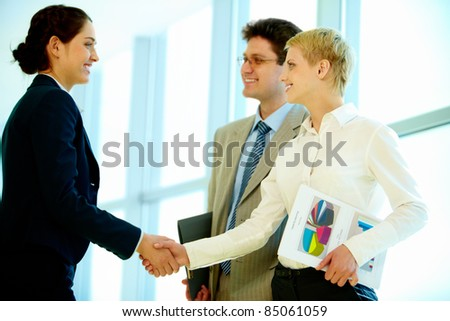 Photo of successful business partners handshaking at meeting