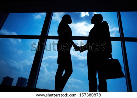 Photo of successful businessman and businesswoman handshaking after striking deal - stock photo