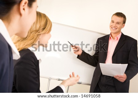 Photo of successful businessman standing at white board while two ladies looking at him during seminar