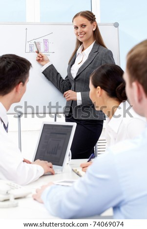 Photo of successful businesswoman reading lecture to his colleagues at presentation of new project