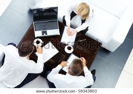 Photo of successful employees discussing business plan at meeting