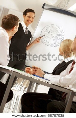 Photo of successful female standing by whiteboard while explaining her idea to colleagues