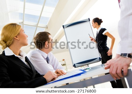 Photo of successful manager standing by whiteboard while the others listening to her
