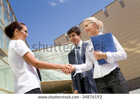 Photo of successful partners handshaking after striking deal at meeting